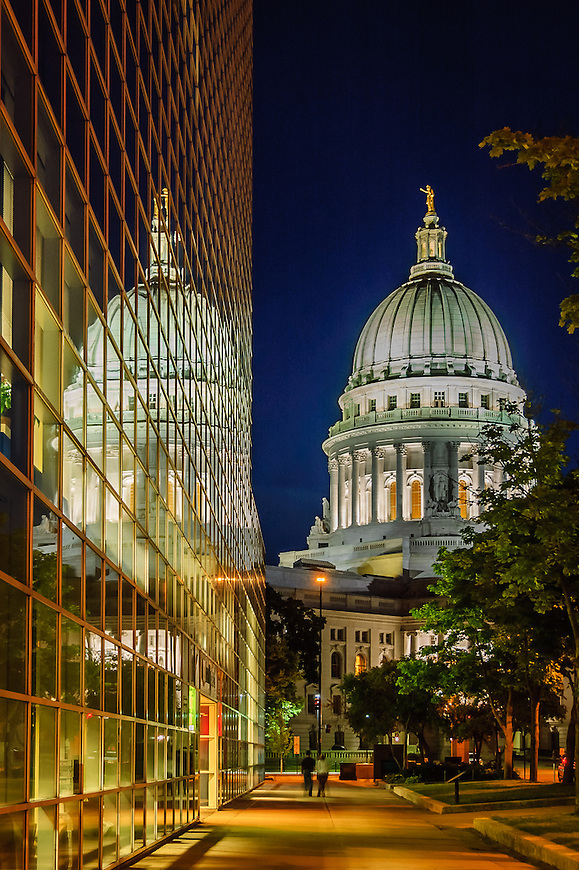 The Wisconsin State Capitol reflected in the windows of a modern building on the Capital Square in Madison, Wisconsin.