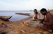 Lake Chaya, Zambia, Africa. Two fishermen reparing their nets with their canoes.