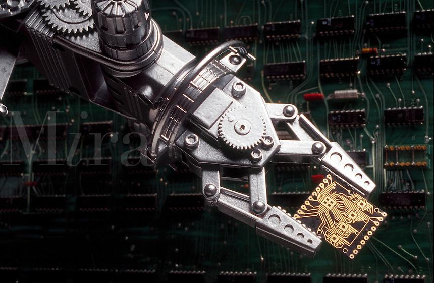 Robotic arm holding a mini circuit board.