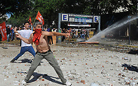 A rioters throws a a stone to police during severe clashes   near the Congress building while Deputies Chamber was   discussing changes in   retirement legislation