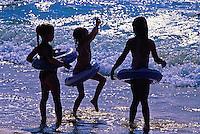 Three girls playing at the beach and having fun