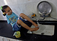 """Gaza.June.09.2008.Aya Masouad 8 years born without arms,use here toes and feet to go around with her daily life,she cleaning dishes after she eat. she easts or drink with her toes , she love her life and thanking God, she practice her life as she is normel people . """" Photo by Fady Adwan/propaimages"""""""
