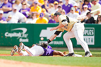 Matt Conway #25 of the Wake Forest Demon Deacons stretches for a wide pick-off throw as Trey Watkins #3 of the LSU Tigers dives back towards first base at Alex Box Stadium on February 20, 2011 in Baton Rouge, Louisiana.  The Tigers defeated the Demon Deacons 9-1.  Photo by Brian Westerholt / Four Seam Images