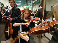 Switzerland. Canton Ticino. Lugano. Conservatorio della svizzera italiana. Orchestra d'Archi Giovanile della svizzera italiana. Two girls and a boy with violins musical instruments are warming-up before the concert. The violin, also known as a fiddle, is a string instrument, usually with four strings tuned in perfect fifths. It is the smallest, highest-pitched member of the violin family of string instruments. Someone who plays the violin is called a violinist or a fiddler. The violinist produces sound by drawing a bow across one or more strings (which may be stopped by the fingers of the other hand to produce a full range of pitches), by plucking the strings (with either hand), or by a variety of other techniques. 14.12.13 © 2013 Didier Ruef