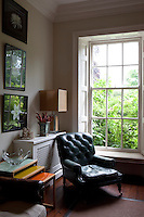 A green leather leather armchair is placed in front of a tall window.