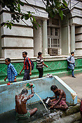 Men bathe along a street in the BBD Bagh area of Kolkata, India, on Friday, May 26, 2017. Photographer: Sanjit Das