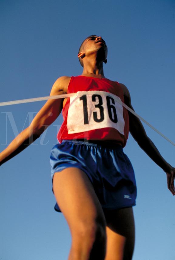 An African-American male runner breaks the finish line ribbon at Lebanon Valley College Track. Runner. Harrisburg Pennsylvania United States.