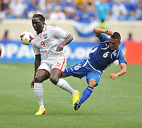 Richard Menjivar Peraza (6) of El Salvador gets fouled by Kenwyne Jones (9) of Trinidad & Tobago.  Trinidad & Tobago tied El Salvador 1-1 in the first round of the Concacaf Gold Cup, at Red Bull Arena, Monday July 8 , 2013.