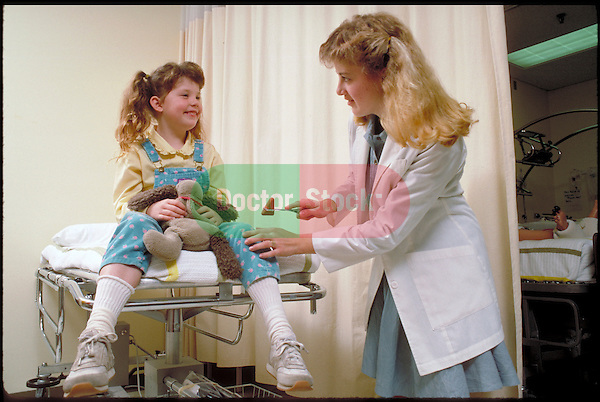 young nurse testing reflexes of child patient