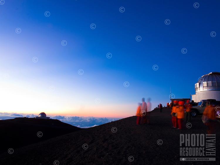A long exposure image of visitors watching the sun set at the top of Mauna Kea, Big Island.