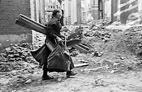 Photo from the NIOD's Huizinga collection. A woman carries firewood from an illegally demolished building during the fuel shortage caused by the national railway strike.