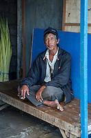Jimbaran, Bali, Indonesia.  Man Resting, Smoking, Jimbaran Fish Market, Early Morning.