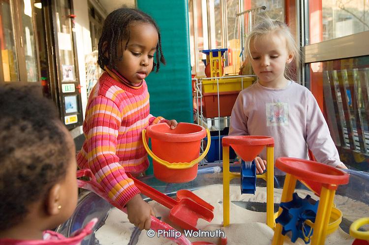 Children play at a sandpit in Warwick Day Nursery, Warwick Estate, Paddington, London