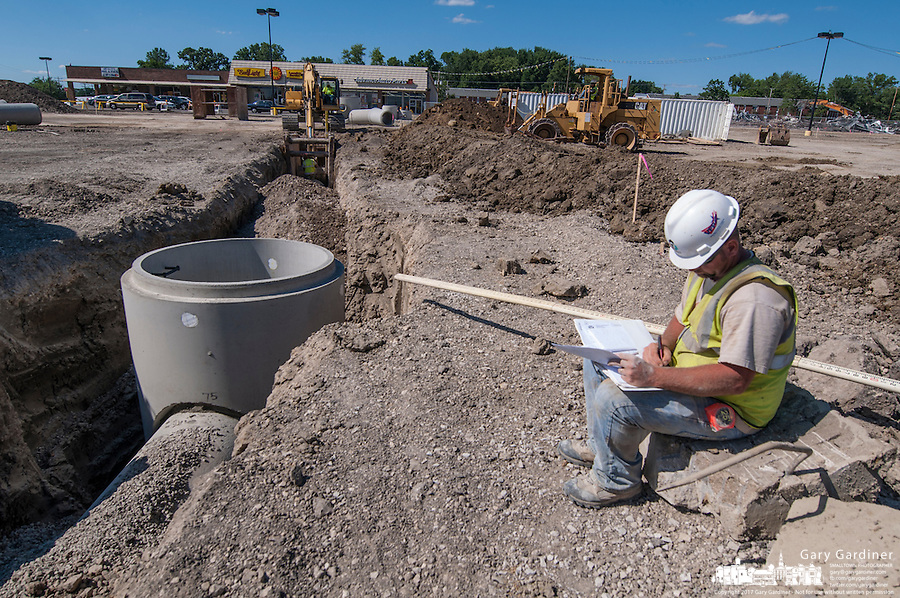 A worker notes progress on new drainage pipes in the parking lot as wrecking crews remove a large portion of Westerville Square Shopping Center to make way for the construction of a new WalMart store in the Columbus suburb. The store will approximately 108,000-square-feet, about half the  size of a traditional WalMart super store..
