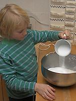Kinder basteln Blattkacheln aus Salzteig, Junge gibt die Zutaten zum Salzteig in eine Schüssel