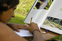 A boy at a rural school in Costa Rica prepares a sketch of a scene that will later be painted onto a mural on the front of the school. The mural is about the need for protecting the environment.