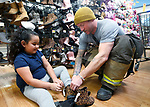 Scott Pellow, with East Fork Fire Protection District, helps Aliyah shop for new boots during the 16th annual Holiday With a Hero shopping day, in Carson City, Nev., on Wednesday, Dec. 18, 2019. The event pairs law enforcement, fire, military and medical officials with homeless children from the Carson City School District McKinney-Vento program for a $100 shopping spree at Walmart.<br /> Photo by Cathleen Allison