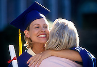 Mother celebrates her daughters graduation with a hug.