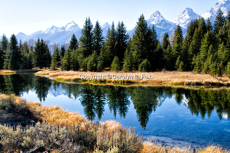 Reflections of The Grand Tetons are seen in the clear blue water.