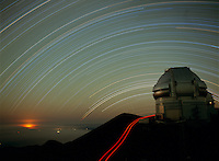 Star trails over the Gemini North Telescope, looking to the south.  The glow from lava from the eruption of Kilauea volcano can be seen on the left.  The trail of a meteor can be seen near the horizon in the right center.