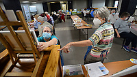 Instructors Helen Eaton (left) and Julie Brandt show how to set up an easel Friday, Oct. 8, 2021, during the Oil Painting for Beginners - Landscape class offered by the University of Arkansas Osher Lifelong Learning Institute at the Fayetteville Executive Airport in Fayetteville. The two-hour class is taught over the course of two sessions with participants learning hands-on how to paint a landscape scene. Visit nwaonline.com/211009Daily/ for today's photo gallery.<br /> (NWA Democrat-Gazette/Andy Shupe)