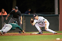 Stetson Hatters first baseman Will Mackenzie (9) catches a pickoff attempt throw as Dan Swain (22) dives back to the bag with umpire Rob Healey looking on during a game against the Siena Saints on February 23, 2016 at Melching Field at Conrad Park in DeLand, Florida.  Stetson defeated Siena 5-3.  (Mike Janes/Four Seam Images)