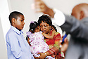 Ashaun Cotton and Debera Jefferson, holding her granddaughter listen while Rev. Aldon Cotton preaches to his congregation about surviving day to day after Hurricane Katrina, 2006.
