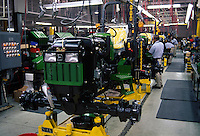 A John Deere tractor assembly line with workers and machinery.