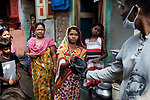 A member of a charitable trust hands over rice and potato to a poor woman at Maniktola slum in Kolkata during 21 days lock down in India due to covid 19 pandemic. Kolkata, West Bengal, India. Arindam Mukherjee.