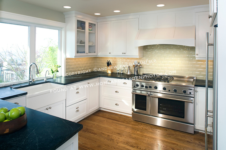 white painted cabinetry, sage geen subway tiles, and oiled soapstone countertops in a newly remodeled, west-facing kitchen with sunlight streaming in