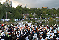 """UKRAINE, Uman, 2008/09..One of the most intensive moments of Rosh Hashanah takes place during """"Tashlich"""" or """"casting off'"""", when thousands of Hasidic pilgrims gather around a lake to symbolically """"cast their sins into the sea."""" The Hasidic tradition, founded in the 18th century in Belarus and Ukraine, places special emphasis on joyous communion with God. The singing and dancing give Uman a festive air. .© Cyril Horiszny / EST&OST"""