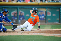 Zach Houchins (12) of the Salt Lake Bees slides home during the game as Johnny Monell (21) of the Las Vegas 51s applies the tag at Smith's Ballpark on May 7, 2018 in Salt Lake City, Utah. The 51s defeated the Bees 10-8. (Stephen Smith/Four Seam Images)