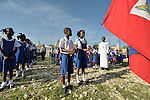 Father Jean-Chenier Dumais, a Russian Orthodox priest in Port-au-Prince, Haiti, stands with children of the Notre Dame de Petits school while they sing the national anthem as Haiti's flag is raised at the beginning of a school day. The school's building collapsed in the January 2010 earthquake, and classes are currently conducted in large tents provided by International Orthodox Christian Charities.