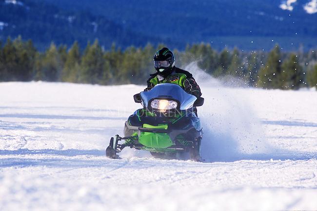 A snowmobile crosses a wide open field in southwest Montana