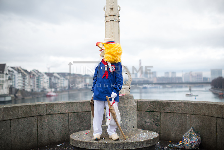 A masked participant in  Fasnacht, the Carnival of Basel, in Switzerland, stands on a bridge over the river Reine, during one of two processions called Cortèges, on the first day of festivities. Feb. 23, 2015.