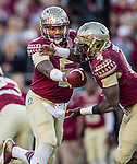 Florida State quarterback Jameis Winston hands the ball off to running back Dalvin Cook in an NCAA football game against Florida in Tallahassee, November 29, 2014.  The Florida State Seminoles defeated the Florida Gators 24-19.