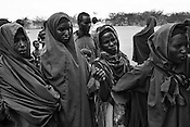 A group of refugees gather to meet the officials for registration outside a food distribution point in IFO camp in Dadaab Refugee camp in northeastern Kenya. Hundreds of thousands of refugees are fleeing lands in Somalia due to severe drought and arriving in what has become the world's largest refugee camp. Photo: Sanjit Das/Panos