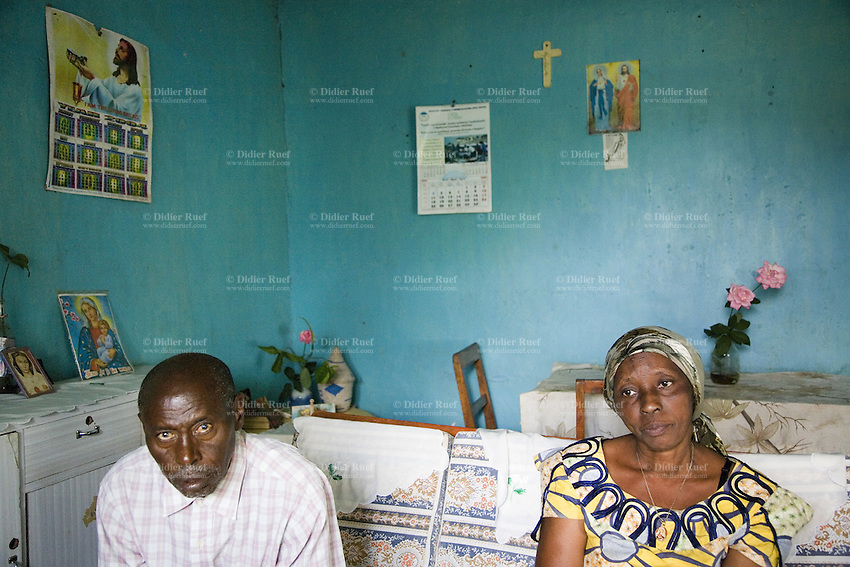 Rwanda. Southern province. Mataba village. Pierre Claver Karenzi is hutu, his wife Marthe is tutsi. Mixed couple, seated on a bench at home. Religious posters on the wall, with representations of Jesus Christ, the Virgin Mary and a catholic Holy cross.  © 2007 Didier Ruef