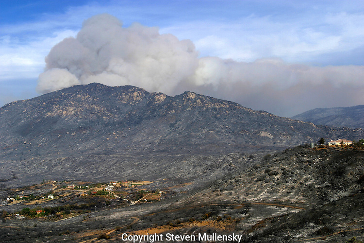 The Valley Center fire east of Escondido left homes standing untouched amid a ruined landscape devastated by a fast moving brush fire. Clearing the brush away from the structures were a main reason these homes were spared.