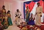 Hindu family in London UK celebrate their 16 year old daughters coming of age party. Ritusuddhi, also called as Ritu Kala Samskara, <br />  Coconut milk is poured onto her head by her brother, who sits of floor with her. This  symbolises health and prosperity, family members stand by her side. Mitcham south London UK