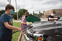 """Grayson Eichelberger (from left), Chloe Riggins and Luke Nesmith wash a truck, Saturday, September 12, 2020 during a fundraiser carwash at Compassion NWA in Springdale. Members of the Shiloh Christian Marching Band held their yearly fundraiser to raise money for travel expenses, competitions and new instruments and music. It is their biggest fundraiser for the year with the goal of raising $1,500, most of which will be saved for next year and for the band's annual end-of-the-year banquet. Last year the band raised about $4,000. """"This year is looking a little different. Normally we use our funds to go to marching contests in the fall,"""" said Angie Haws, a marching band mom. """"We're hoping to use the money in the spring because we're hoping things will happen for us in the spring. Anyone looking for more information about the band program can contact band director Stephen Hunt at stephenh@shilohsaints.org. Check out nwaonline.com/200913Daily/ for today's photo gallery. <br /> (NWA Democrat-Gazette/Charlie Kaijo)"""