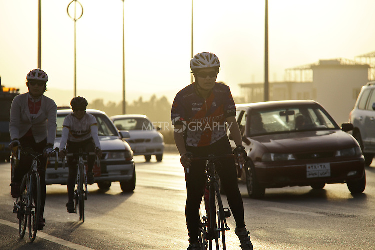 SULAIMANIYAH, IRAQ: Cyclists from the Newroz Club on a road in Sulaimaniyah during an evening training session. Nyan Yassin is second left.<br /> <br /> Nyan Yassin, 24, is a professional competitive cyclist in Sulaimaniyah in the semi-autonomous region of Iraqi Kurdistan.  She is the captain of an all-female club called Newroz Club, which is the only cycling club for women in Sulaimaniyah, although there are other clubs around Iraq.  She trains and competes on roads that are badly surfaced and busy with traffic.<br /> <br /> Nyan was the first woman to start cycling in Sulaimaniyah.  She was always competitive and after trying her hand at different sports she settled on cycling.  She is now the top female cyclist in Iraq.  Her nickname is MigMig after the noise made by the cartoon character Roadrunner.<br /> <br /> Despite being clearly talented at her sport Nyan knows that in a couple of years she will have to get married and then abandon it as, in the traditional society that Kurdistan is, being a wife and a competitive sportswoman at the same time is not an option.<br /> <br /> Photo by Gona Hassan/Metrography