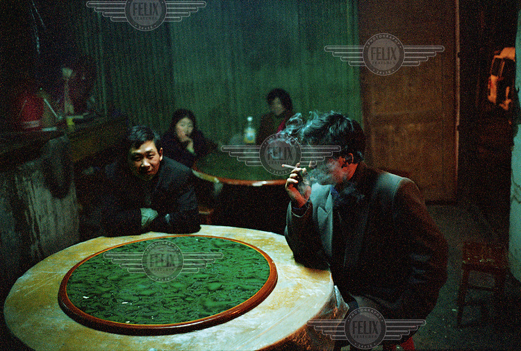 Few remaining inhabitants of the town sit in a bar.  Most of the local community has been relocated in order to make way for the Three Gorges Dam project, which will raise the water levels of the river and inundate lower-lying areas.