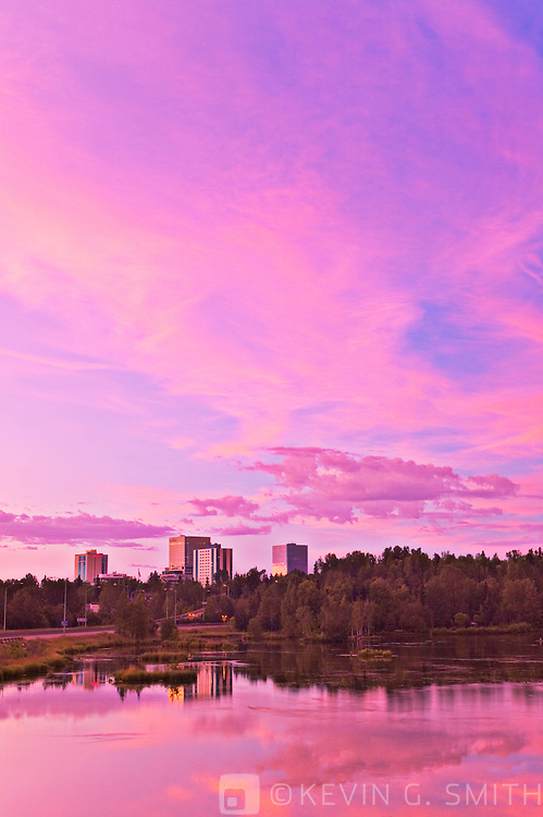 Anchorage city skyline and reflection in Westchester Lagon at sunset, blured traffic lights, summer, Anchorage Alaska.