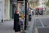 Woman wearing a face mask and disposable gloves at a bus stop in West Hampstead, London
