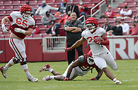 Arkansas running back Dominique Johnson (right) carries the ball Saturday, April 3, 2021, as defensive lineman Taurean Carter reaches to make the tackle during a scrimmage at Razorback Stadium in Fayetteville. Visit nwaonline.com/210404Daily/ for today's photo gallery. <br /> (NWA Democrat-Gazette/Andy Shupe)