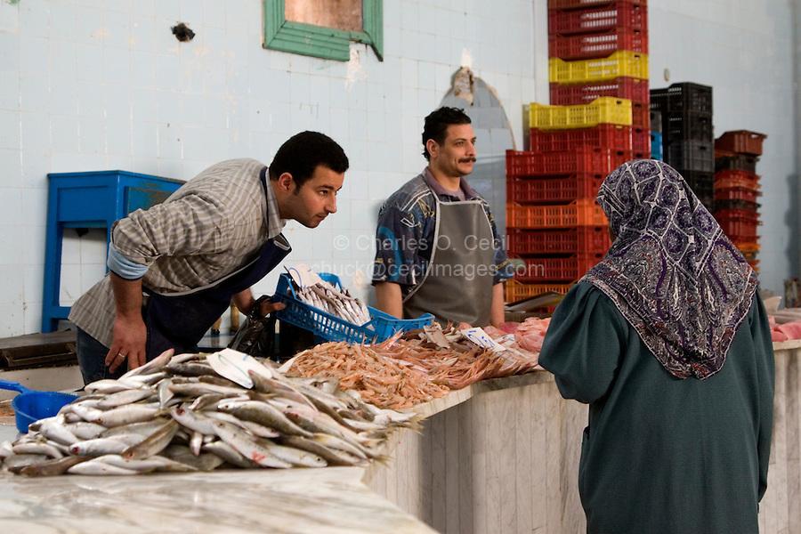 Tripoli, Libya - Fish Market, Rashid Street.  Discussing a Sale with a Customer.