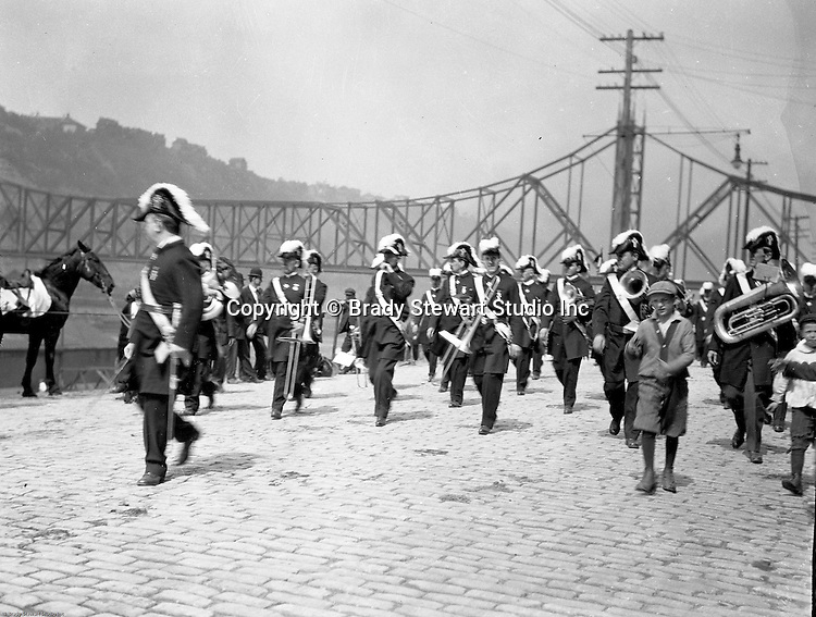 Pittsburgh PA:  Pittsburgh-area Manson marching in the annual St Patrick's Day Parade.  View of Masonic Band marching down Water Street with children walking alongside the troop. The new Wabash Bridge in the Background.