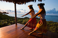 Young women practicing hula in a beachfront gazebo at sunset