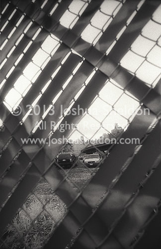 Cars through chain link fence<br />